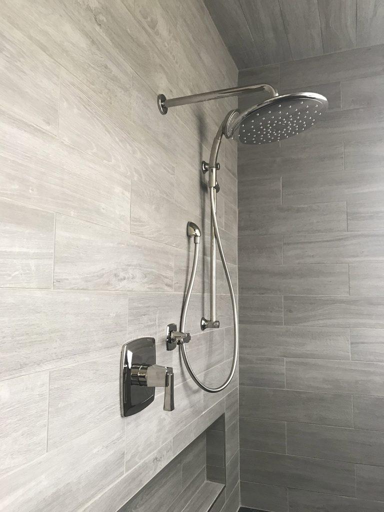 Gray wood-look tile shower with polished nickel plumbing fixtures.
