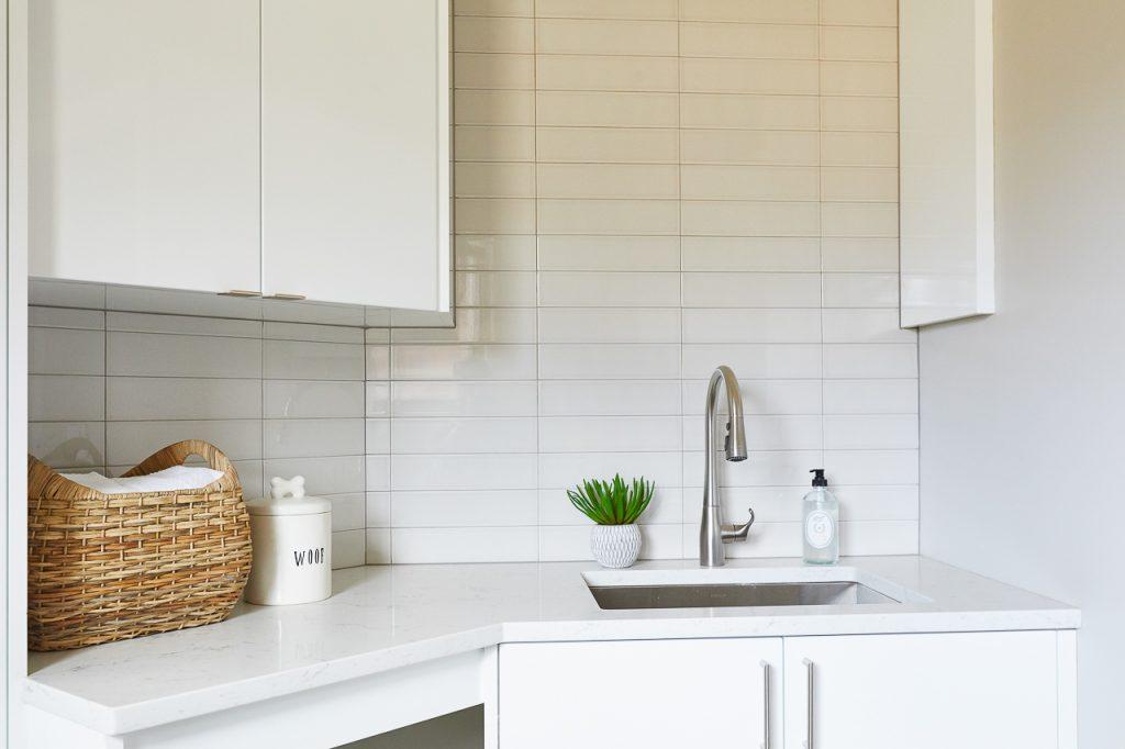 Modern white laundry room, gray subway tile backsplash
