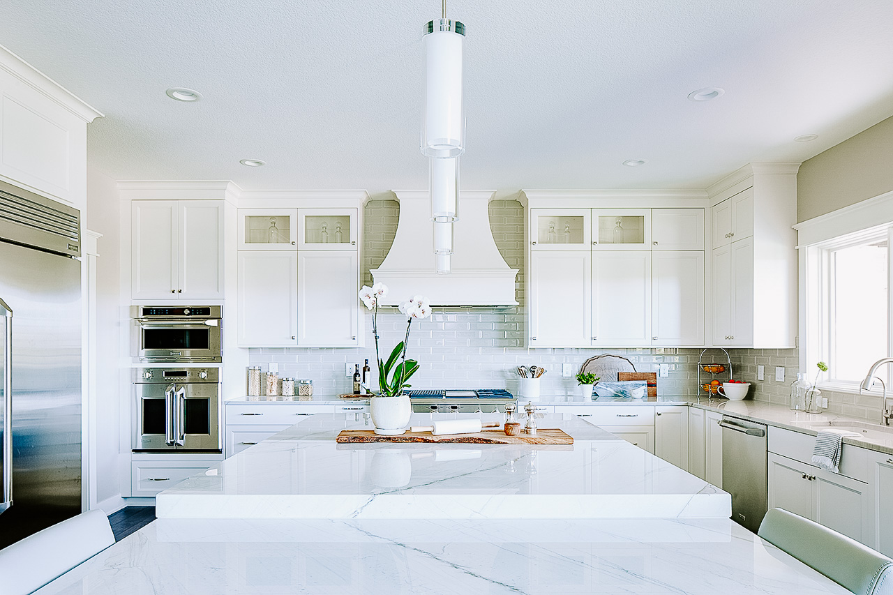 Large white kitchen with quartzite drop down island by Jillian Lare Interior Design