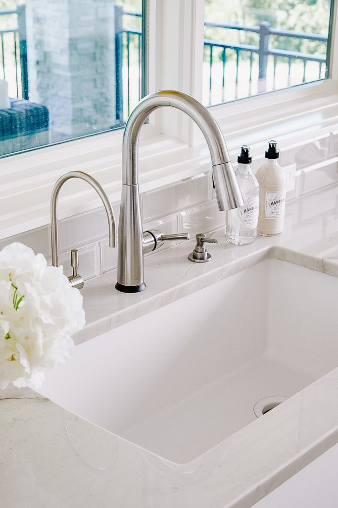 Under-mount sink in front of windows with stainless faucet, quartzite countertop