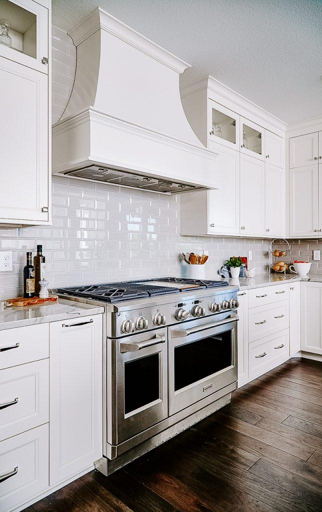 Custom cabinetry style hood, white kitchen, dark hickory floors